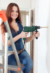 Happy girl drills hole in  wall