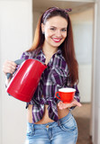 happy pretty housewife with tea kettle and cup