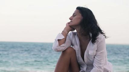 Pensive, sad beautiful woman on the beach