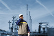 oil and gas worker in front of large refinery industry