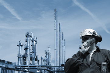 industry worker in front of large oil and gas refinery