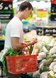 man with basket full of food in supermarket