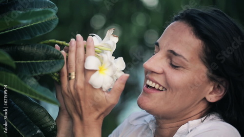 Happy young woman smelling beautiful white flowers on tree