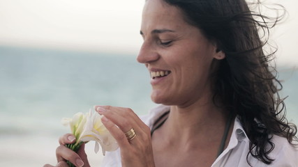 Happy young woman smelling beautiful white flower on the beach