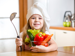 child girl weared as cook with vegetables at kitchen