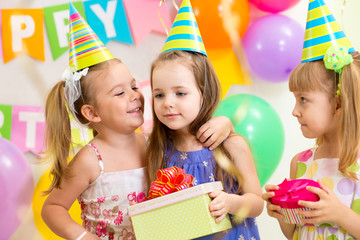 pretty children giving gifts on birthday party