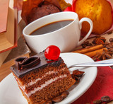 Chocolate cake and cup of coffee with books and autumn leaves