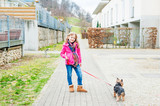 Outdoor portrait of a cute little girl with a pet dog