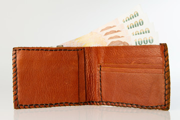 Brown wallet with Thai Baht Paper Currency on the white backgrou