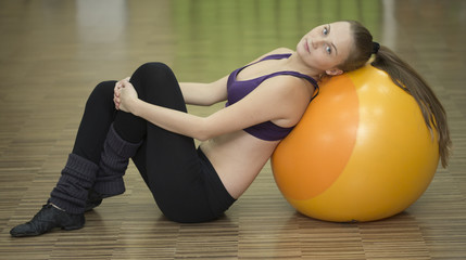Young athlete woman taking rest on fitness ball