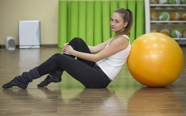 Young athlete woman sits on floor at fitness ball