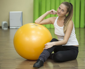 Young athlete woman sits on floor with fitness ball