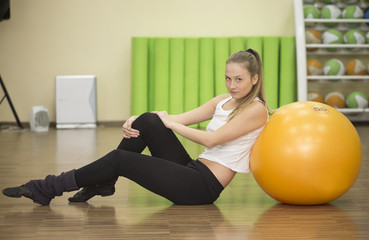 Young athlete woman sits on floor with ball