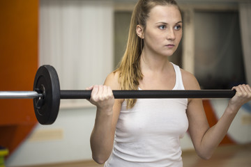 Young athlete woman exercising with barbell