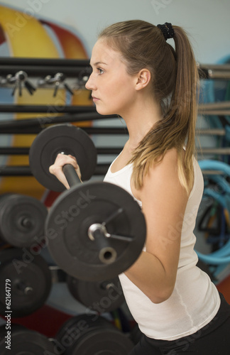Young athlete woman working with barbell