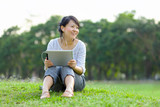 Woman holding digital tablet in park