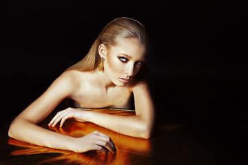 Портрет девушки с золотым макияжем на чёрном фоне
