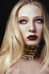 Портрет блондинки с золотым макияжем и колье на чёрном фоне