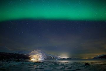 Green aurora borealis over a frozen fjord