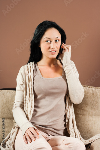 Woman sitting on the sofa and talking on the phone