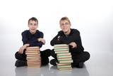 Two teenagers with stacks of books sitting on the floor
