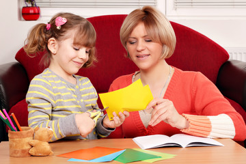 happy mother and daughter cutting paper