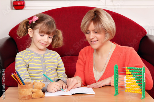 happy mother and daughter doing homework