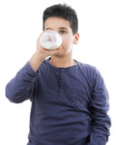Child drinking glass of milk isolated on white background