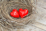 Two red hearts in a bird nest on wooden board