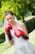 Bride with red boxing gloves in park