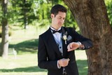 Attractive groom checking time in garden