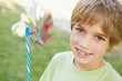 Close-up of smiling boy holding pinwheel in park