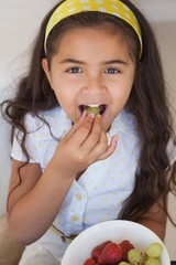 Close-up portrait of a smiling girl eating fruits
