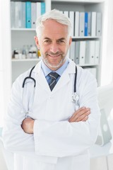 Portrait of a smiling confident male doctor at medical office