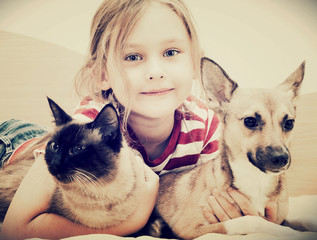 child hugging a cat and dog