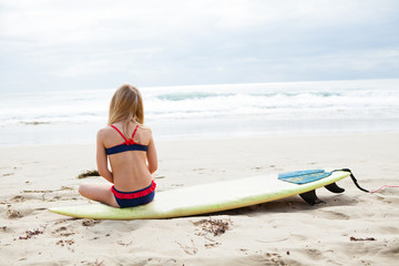 Young girl sitting on surfboard on beach