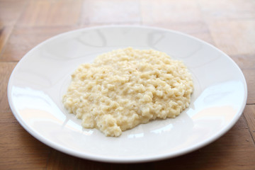 risotto dish with herbs on wood background