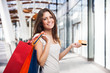 Woman holding shopping bags and a credit card