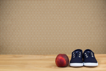 Sneakers and peach on wooden table over vintage wallpaper