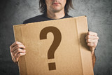 Man holding cardboard poster with question mark