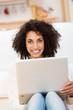 glückliche junge frau mit laptop zu hause