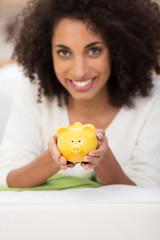 attraktive frau hält gelbes sparschwein in der hand