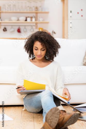 junge frau liest zuhause in unterlagen