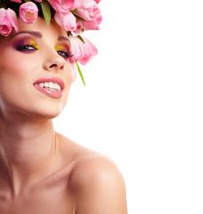 Portrait of a beautiful spring girl wearing flowers hat. Studio
