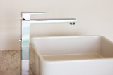 An abstract detail of a contemporary wash-hand basin and faucet