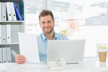 Handsome man working at his desk on laptop smiling at camera
