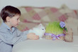 child plays with little fluffy white rabbit near the flowerpot w