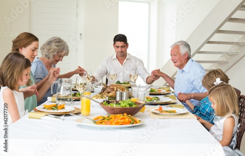 Family praying together before meal at dining table
