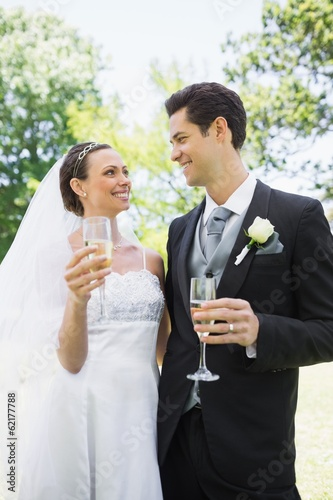 Romantic bride and groom having champagne in park