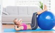 Cheerful fit blonde doing sit ups with exercise ball